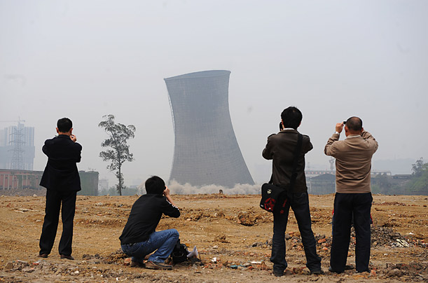 Spectators watch the destruction of a cooling tower in the Huaneng Heat and Power Plant in Chengdu, China.