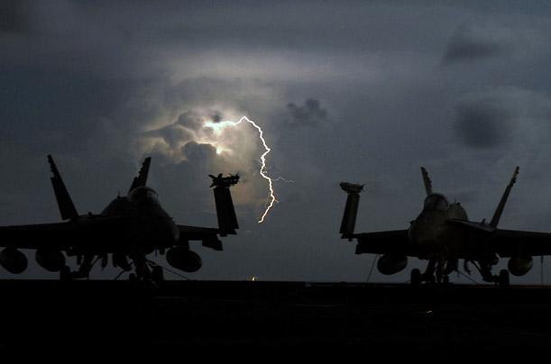 Lightning strikes behind two F/A-18C Hornet aircraft on the flight deck of the Nimitz-class aircraft carrier USS John C. Stennis on the Pacific Ocean.