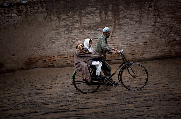 A Pakistani man pushes his bicycle and his daughters along a muddy street in Peshawar.
