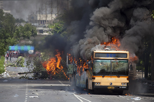A Bangkok bus burns out of control after being set on fire by anti-government demonstrators.