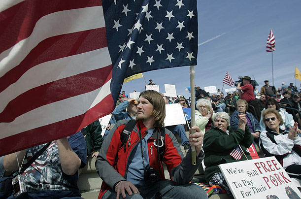 Patrick Will of Eaton, N.Y., holds an American flag during a tax day tea party rally in Albany.