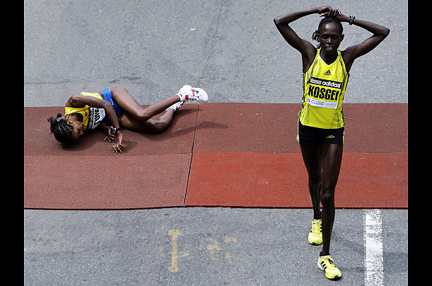 Dire Tune of Ethiopia, left, falls after crossing the finish line in second place behind Salina Kosgei of Kenya who eked out a narrow victory in the women's division of the 113th Boston Marathon.