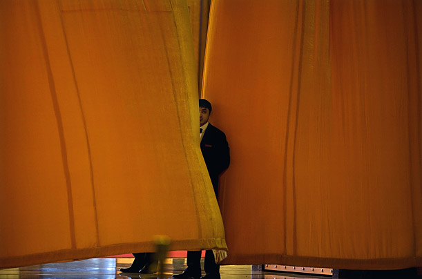 A Chinese usher watches from behind curtains before the start a welcoming ceremony for foreign heads of state at the Great Hall of the People in Beijing.