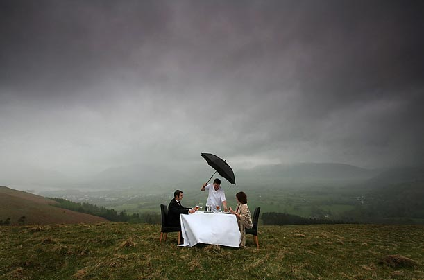 Lake District celebrity chef Peter Sidwell braves the rain as he poses while serving up one of his culinary delights to diners Dawn Titley and Dan Hartley on the summitt of Latrigg in Keswick, England.
