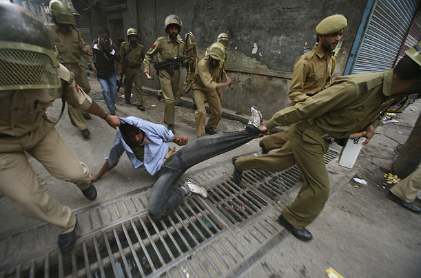 Policemen detain a Kashmiri protester during a demonstration against the Indian general elections.