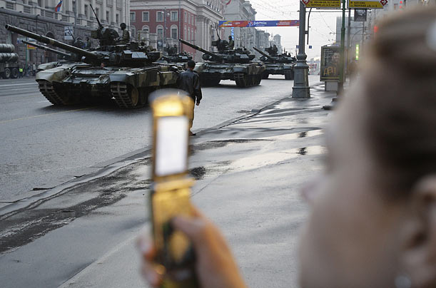 A woman takes pictures of Russian tanks during a rehearsal for the May 9 Victory Day parade in downtown Moscow.