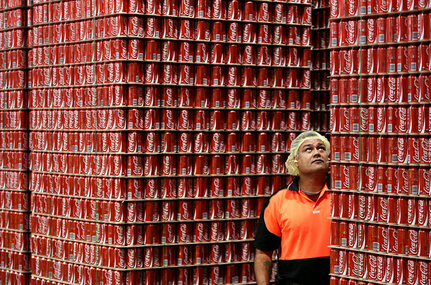 An employee inspects skids of Coca-Cola ready for dispatch from a bottling plant in Sydney, Australia.