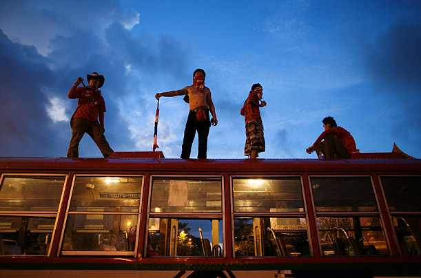 Supporters of Thailand's former Prime Minister Thaksin Shinawatra stand on a bus outside Government house during anti-government demonstrations in Bangkok.