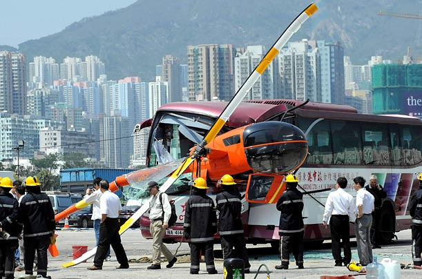 A small helicopter crashed into a parked tour bus while landing at the former Kai Tak airport in Kowloon, leaving 3 injured.