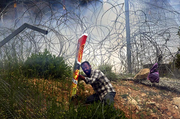 A Palestinian protests the construction of the controversial Israeli separation barrier as Israeli security forces respond with tear gas and rubber bullets.