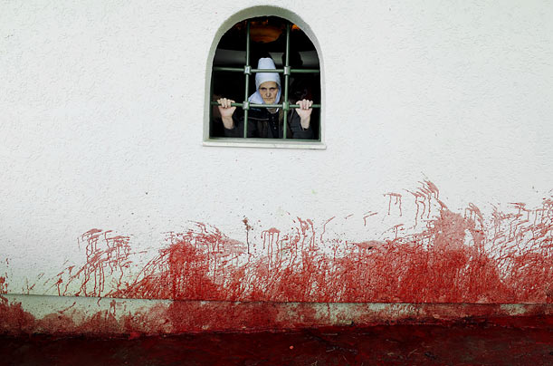 A Kosovo Albanian woman looks out a window in the village of Babaj Bokes after sheep were slaughtered in celebration of Saint George's Day.