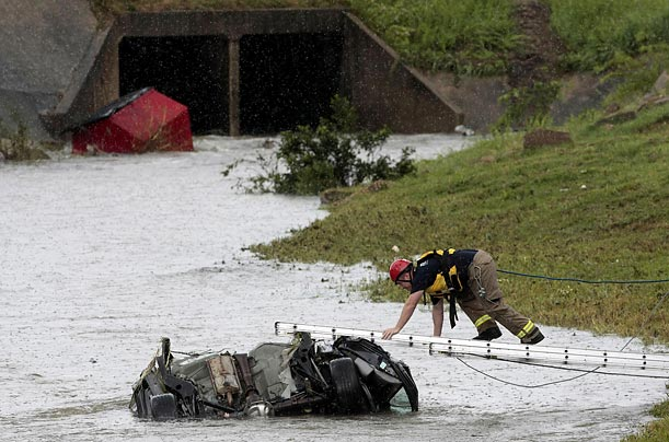 A member of the Montgomery, Alabama Fire Department Heavy Rescue Squad climbs to a car to check for signs of life after it was swept into a drainage ditch by flash floods.