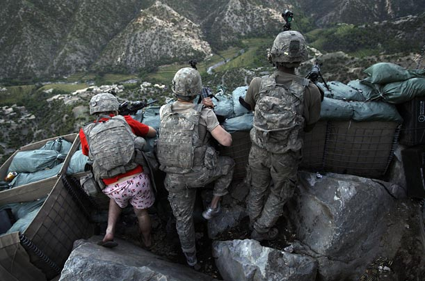 A US soldier is wearing 'I Love NY' boxer shorts after rushing from his sleeping quarters to join his fellow platoon members after they received fire from Taliban positions in the Korengal Valley.