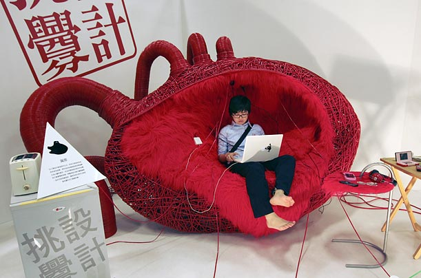 A designer sits in a heart-shaped chair she created at the 2009 Young Designers Exhibition in Taipei, Taiwan.