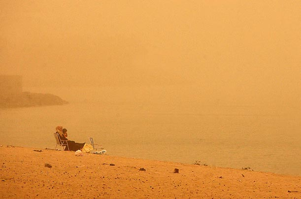 A woman and child sit on a beach during a heavy sandstorm in Kuwait City.