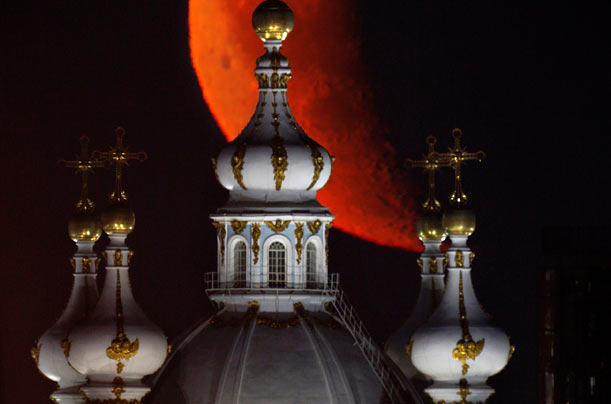 The moon rises behind the domes of the Smolny Cathedral in St. Petersburg, Russia.