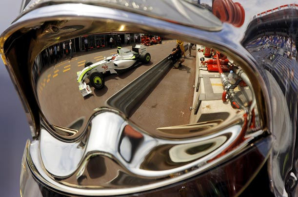 A Formula 1 car is reflected in the mirrored helmet of a firefighter during a practice session for the Monaco Grand Prix in Monte Carlo.