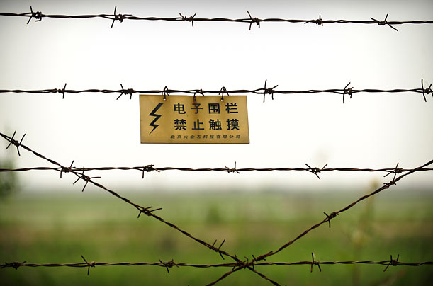 A warning sign on a barbed-wire fence