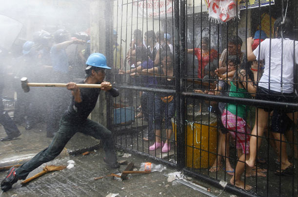 Residents of a government tenement building in Manila, Philippines resist eviction as a demolition worker tries to force their gate open.