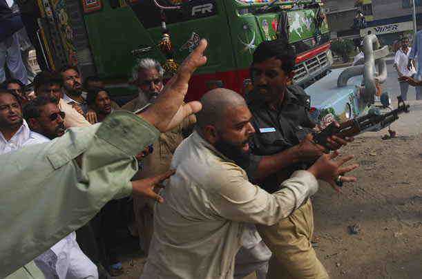Pakistani civilians try to rescue a police officer from an angry mob during a clash between police and protesters in Karachi, Pakistan.