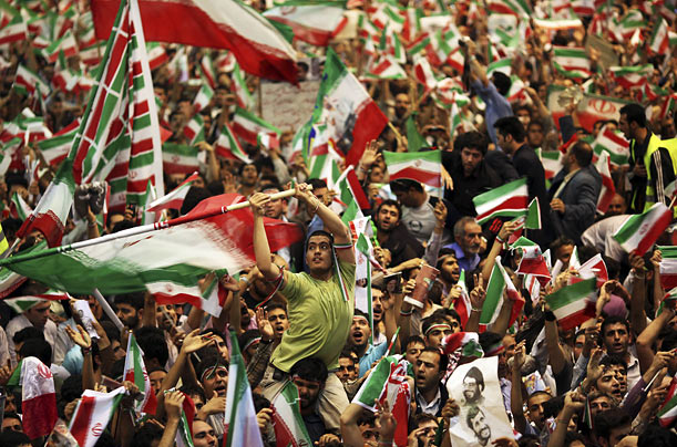 Supporters of Iranian President Mahmoud Ahmadinejad, who faces reelection on June 12th, shout slogans and wave flags during their final gathering in Tehran.