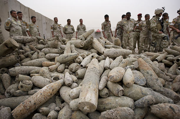 Iraqi Army soldiers gather around thousands of Saddam Hussein-era mortar rounds found in southern Baghdad.
