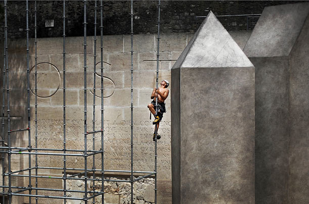 A worker climbs scaffolding on the grounds of the University in Geneva, Switzerland.