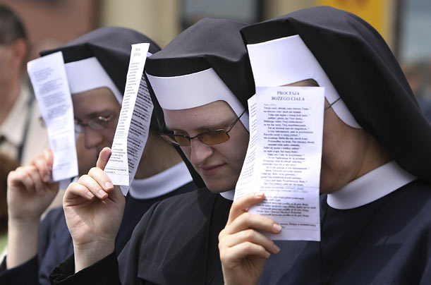 Roman Catholic nuns pray in front of St. Anne's church during the Corpus Christi procession in Warsaw, Poland.