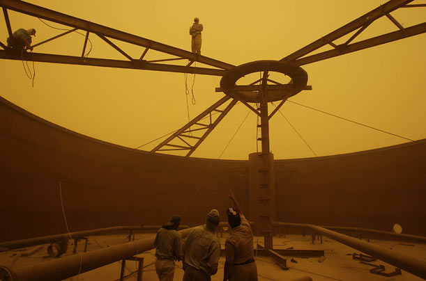 Workers build construction frameworks for gas pipes during a sandstorm southeast of Baghdad.