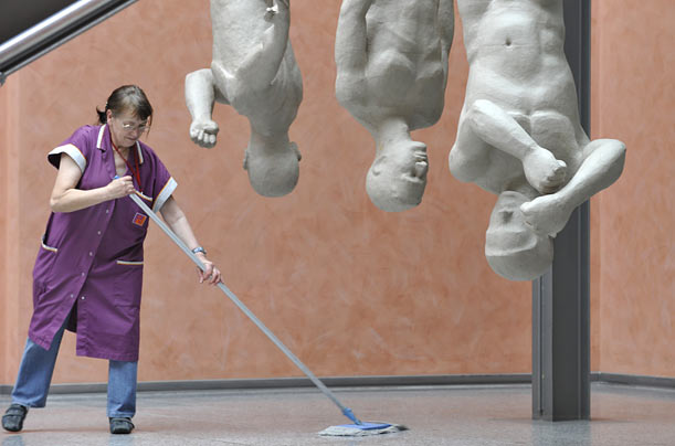 A service staff member cleans the floor near the sculpture group