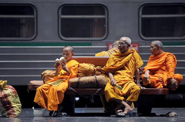 Thai Buddhist monks and a novice sit on a bench after train workers went on strike at Hua Lampong train station in Bangkok.