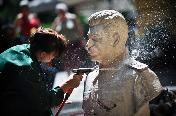 An employee of the Bulgarian National Art Gallery in Sophia cleans a bust of Soviet dictator Joseph Stalin, part of an upcoming exhibition called