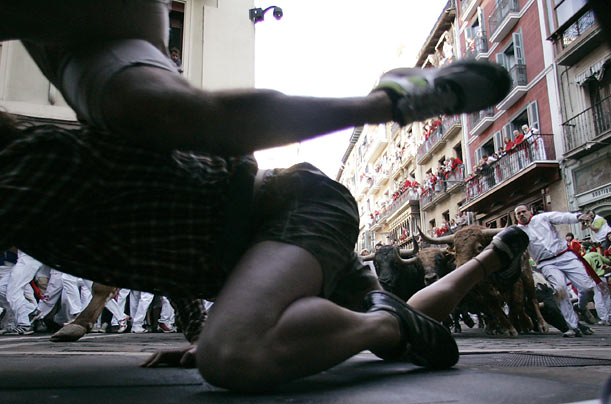 A runner falls in the street on the third day of the running of the bulls at the San Fermin festival in Pamplona, Spain.