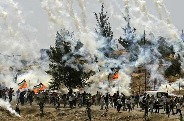 Palestinians, Israelis and foreign demonstrators run from tear gas fired by Israeli troops during a protest against Israel's separation barrier in the West Bank village of Bilin.
