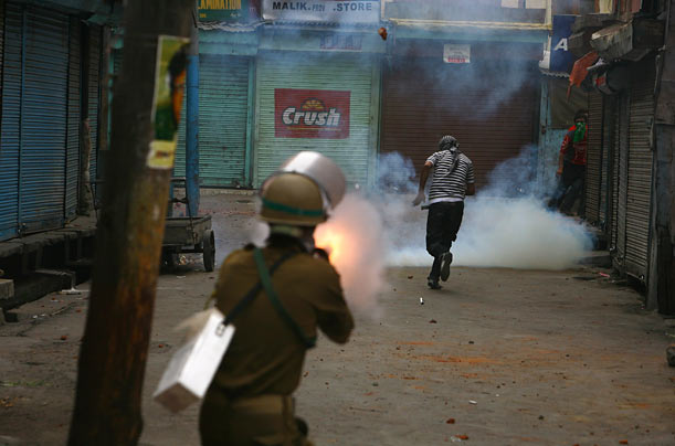 A Kashmiri Muslim runs for cover as an Indian policeman fires a tear gas grenade during protests in Srinagar, the capital of Indian Kashmir