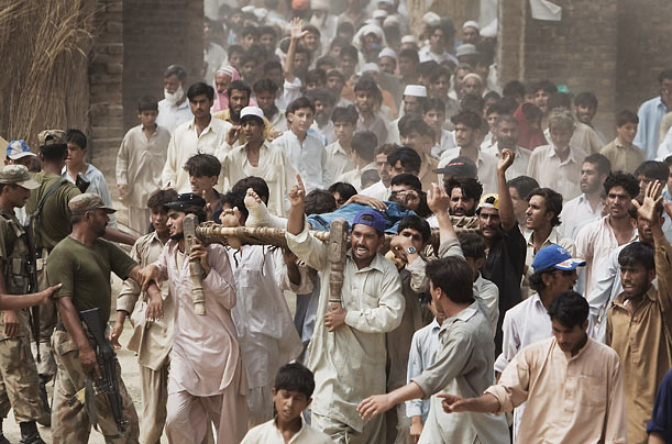 An angry mob carries an injured man from Swat, who according to bystanders, was beaten by police for merely requesting his food