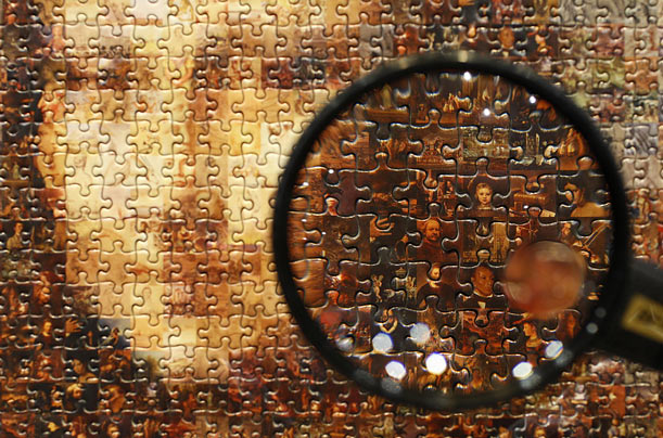 A magnifying glass shows individual paintings forming a puzzle mosaic of the Mona Lisa at the International Tokyo Toy Show.