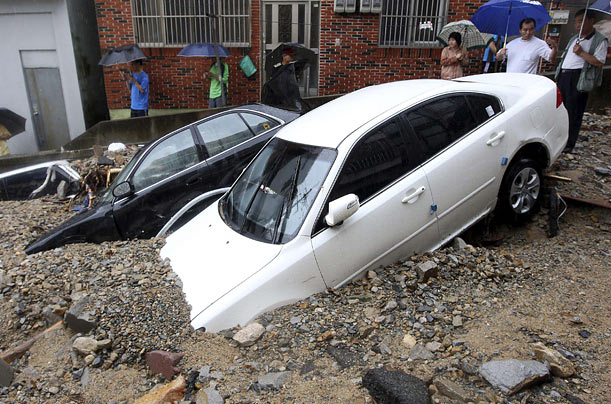 Residents look at cars partially buried in soil and gravel after floodwaters swept them off a street, following heavy rain in Busan, South Korea.