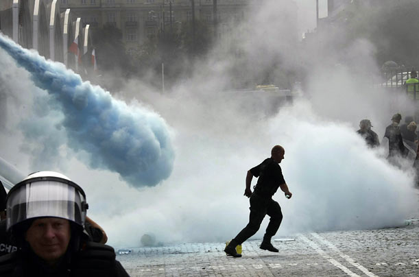 Warsaw security personnel attempting to evict merchants from a condemned bazaar are repelled with fire extinguishers.