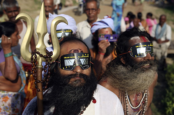 Sadhus, or Hindu holy men, watch the solar eclipse through specially designed viewing glasses in Allahabad, India.