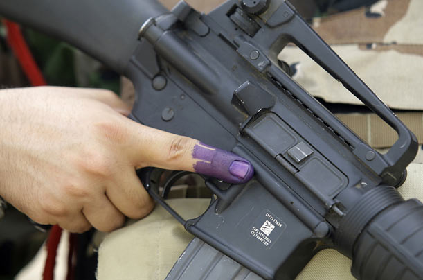 A Kurdish Peshmerga soldier displays an ink-stained finger after voting during a regional parliament election in Baghdad.