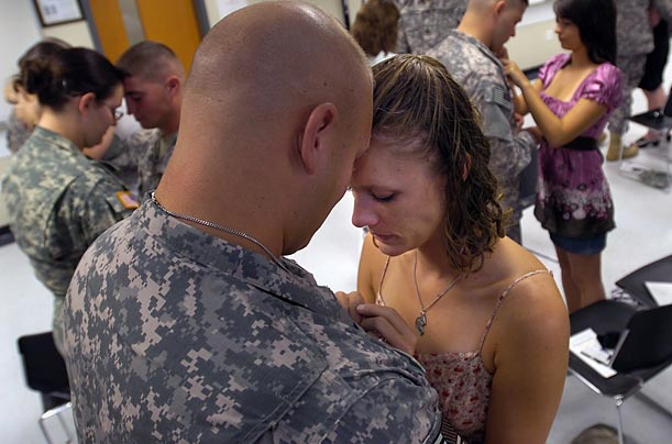A couple, married just over a month, exchange half of a pewter coin, symbolizing fidelity, during a ceremony at Fort Stewart, Georgia. The soldiers deploy to Afghanistan early next week.