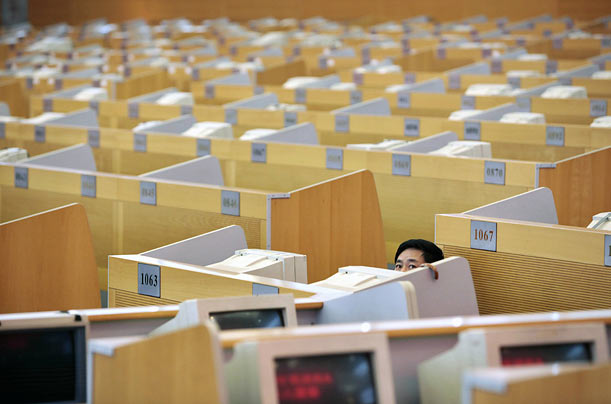 A man looks at an electronic board in the Shanghai Stock Exchange.