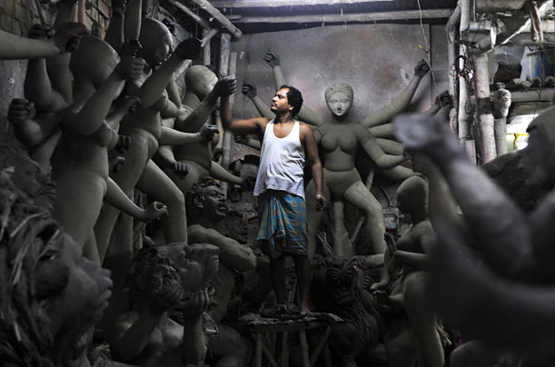 An Indian idol maker works on a semi-finished clay statue of Hindu goddess Durga in Kumartoli, the idol makers' village, in Calcutta.
