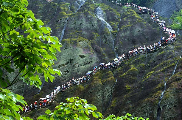 Tourists slowly make their way up a steep path at Mount Wuyi, a famous site in China's Fujian Province.