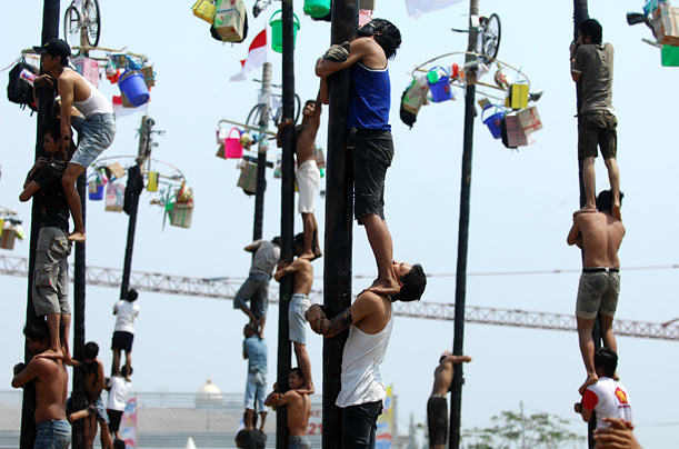 Contestants in Jakarta help one another climb greasy poles to reach prizes at the top during celebrations of Indonesia's Independence Day.