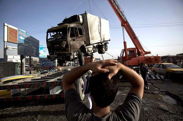 A boy looks at a damaged truck being removed from the site of a suicide bomb blast, which killed seven and injured over fifty, in Kabul, two days before the Presidential elections.
