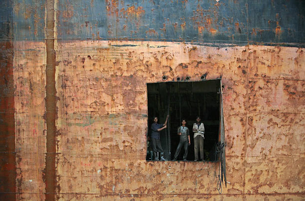 Workers peer out a hole cut in an old vessel at a ship breaking yard in Chittagong, Bangladesh.