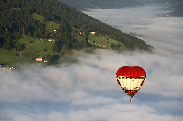 People participate in Balloon-Trekking near Immenstadt, Germany. Passengers sail in a balloon then hike back to their base with little