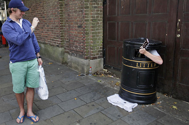 A tourist takes pictures as a street musician performs from inside a trash receptacle in Cambridge, England.